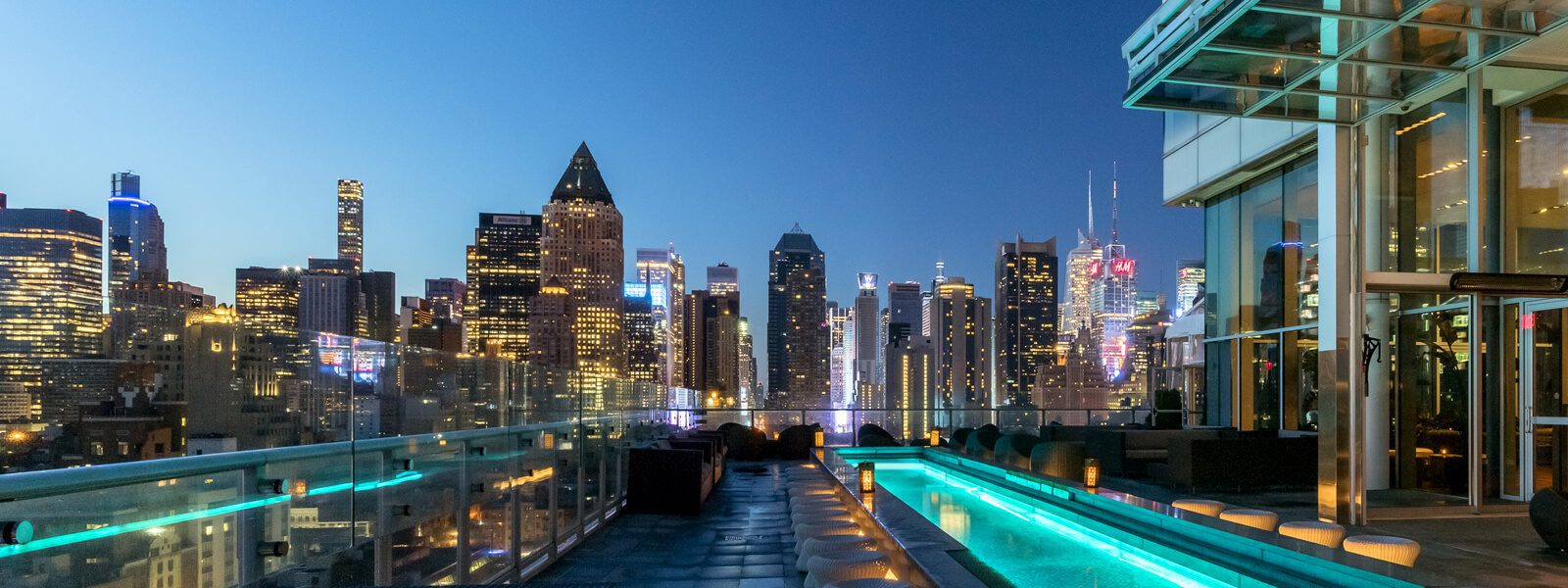 Panorama of Manhattan nighttime skyline from view of terrace with reflecting pool illuminated.