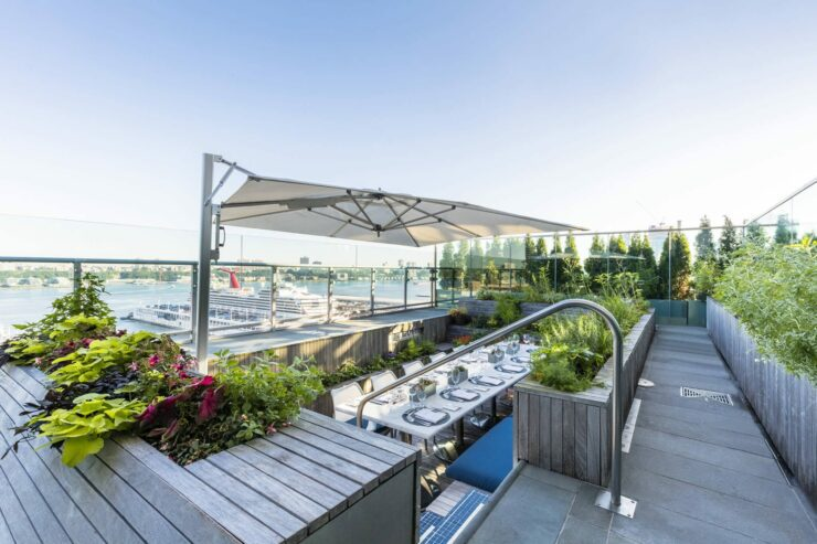 Wide angle of rooftop garden set for dining with umbrella open.